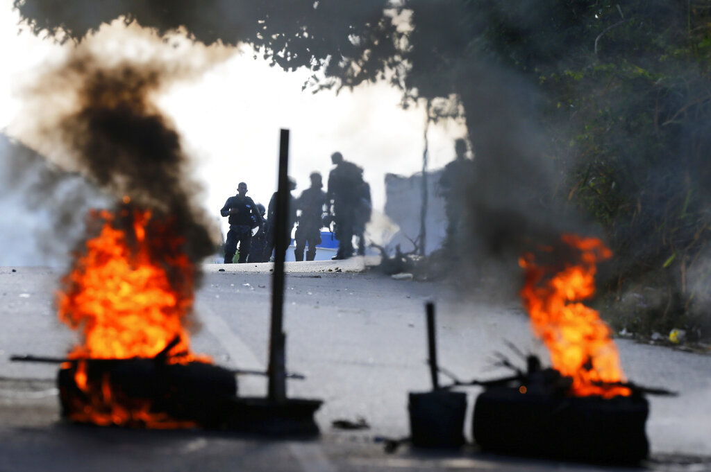 Bolivarian National Police stand behind a burning roadblock set up by anti-government protesters who are showing support for a mutiny by some National Guard soldiers in the Cotiza neighborhood of Caracas, Venezuela, Monday, Jan. 21, 2019. Venezuela's government said Monday it put down the mutiny. (AP Photo/Fernando Llano)