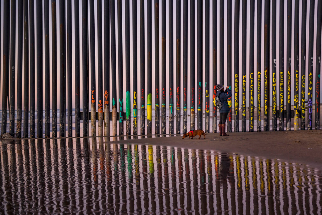 "In this Jan. 3, 2019, file photo, a woman takes a photo by the border fence between San Diego, Calif., and Tijuana, as seen from Mexico. The top House Republican says a bipartisan border security compromise that Congress hopes to produce doesn't have to include the word ""wall."" (AP Photo/Daniel Ochoa de Olza, File)"