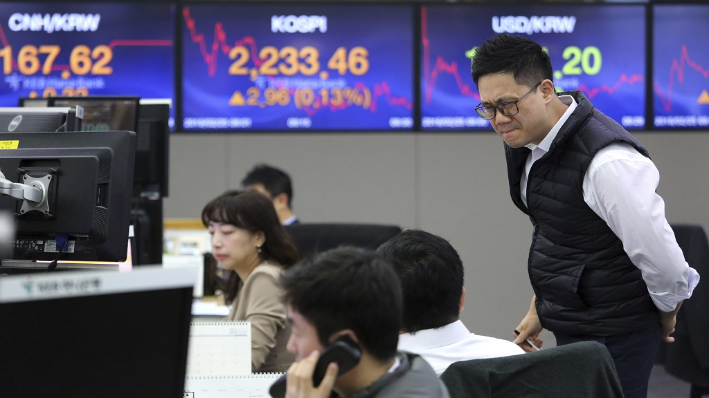 A currency trader watches monitors at the foreign exchange dealing room of the KEB Hana Bank headquarters in Seoul, South Korea, Monday, Feb. 25, 2019. Most Asian stock markets rose Monday after U.S. President Donald Trump said he would postpone a March 1 deadline for a U.S. tariff hike on Chinese imports following weekend talks on a battle over Beijing's technology ambitions. (AP Photo/Ahn Young-joon)