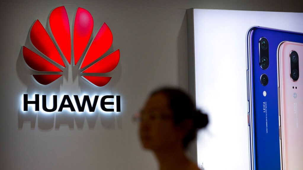 In this July 4, 2018, file photo, a shopper walks past a Huawei store at a shopping mall in Beijing. (AP Photo/Mark Schiefelbein, File)