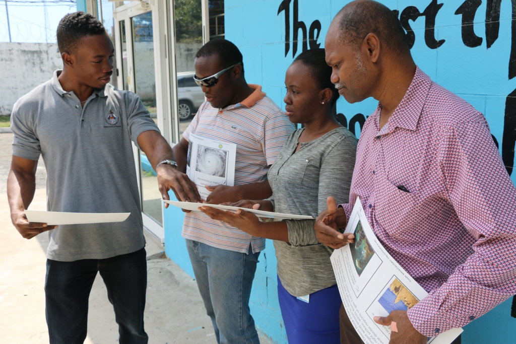 Jamaica Society for the Blind (JSB) librarian Kamika Brathwaite reads the braille on a poster that compares dandelion dispersal to comets as Nathan Henderson (left), president of the Astronomical Association of Jamaica (AAJ), explains the phenomenon. Also experiencing space through their fingertips are JSB assistant librarian Damion Rose and executive director Conrad Harris (right).