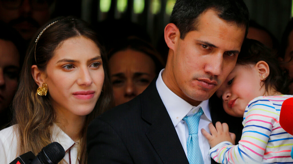 Opposition National Assembly President Juan Guaido, accompanied by his wife Fabiana Rosales and his 20-month-old daughter Miranda, listens to a reporter's question during a news conference outside their apartment, in Caracas, Venezuela, Thursday, Jan. 31, 2019. (AP Photo/Fernando Llano)