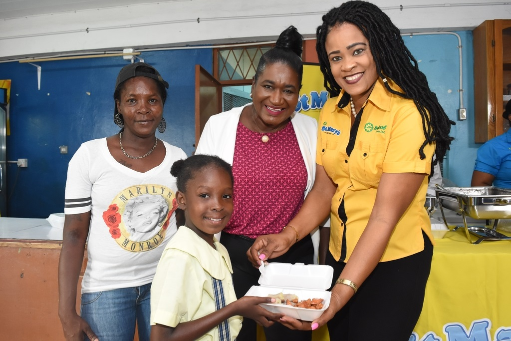 Neleta White (right), national sales manager at Jamaica Producers (JP) Tropical Foods Ltd serves up frank and beans with green bananas to grade 4 student Shauna Kay McKay (second right) during the Eat Well with JP breakfast event at John Mills Infant, Primary and Junior High last month.