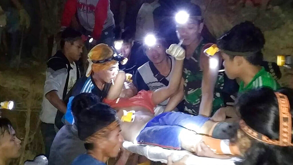 In this undated photo released by Indonesian Search And Rescue Agency (BASARNAS) rescuers evacuate a survivor from inside of a collapsed gold mine in Bolaang Mongondow, North Sulawesi, Indonesia. (BASARNAS via AP)