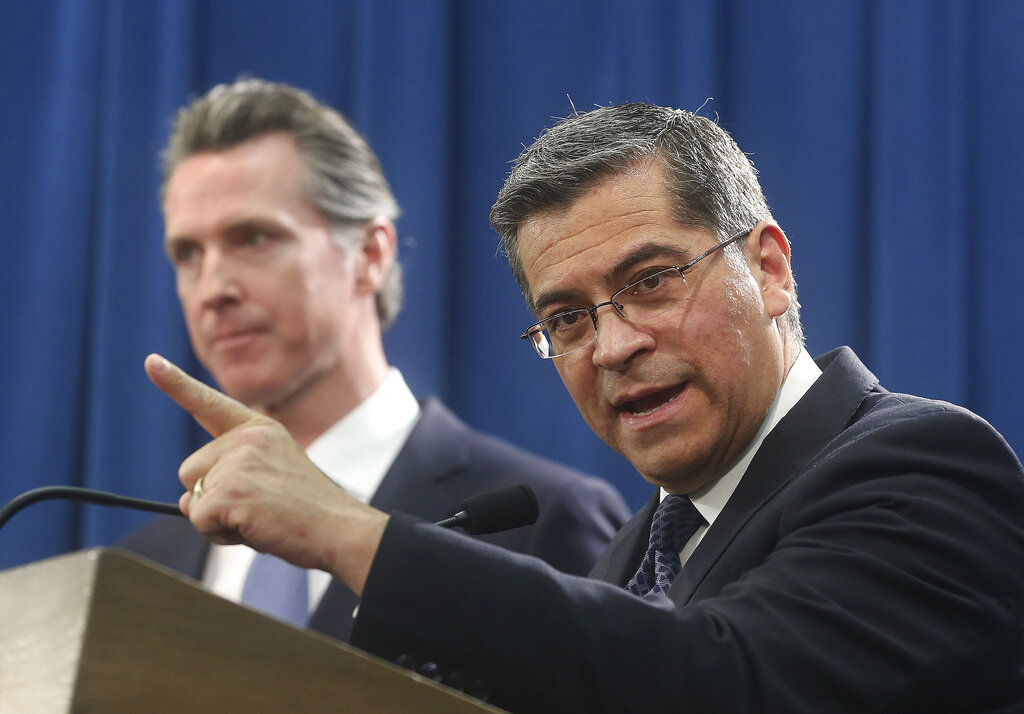FILE - In this Feb. 15, 2019 photo, California Attorney General Xavier Becerra, right, accompanied by Gov. Gavin Newsom, said California was probably suing President Donald Trump over his emergency declaration to fund a wall on the U.S.-Mexico border in Sacramento, Calif. Becerra filed a lawsuit Monday, Feb. 18, against Trump's emergency declaration to fund a wall on the U.S.-Mexico border. (AP Photo/Rich Pedroncelli, File)