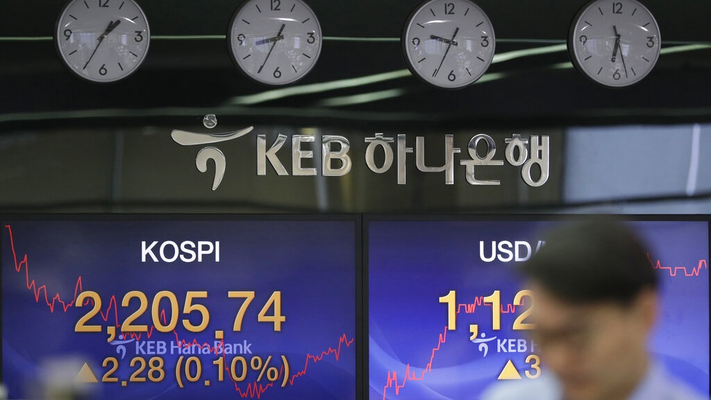 A currency trader walks by screens showing the Korea Composite Stock Price Index (KOSPI), left, and the foreign exchange rate between U.S. dollar and South Korean won at the foreign exchange dealing room in Seoul, South Korea, Thursday, Feb. 7, 2019 (AP Photo/Lee Jin-man).