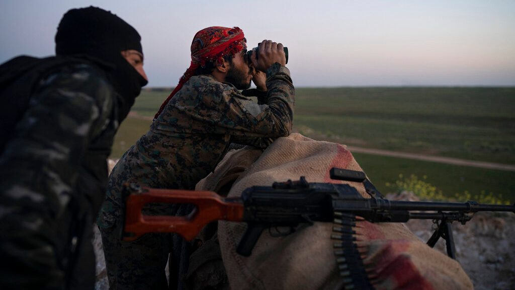 U.S.-backed Syrian Democratic Forces (SDF) fighters watch as an airstrike hits territory still held by Islamic State militants in the desert outside Baghouz, Syria, Tuesday, Feb. 19, 2019. By sundown, there was no sign of any civilians coming out. On the other side of the IS-held pocket, an airstrike was launched by the U.S.-led coalition, increasing the pressure on the militants holding out. (AP Photo/Felipe Dana)
