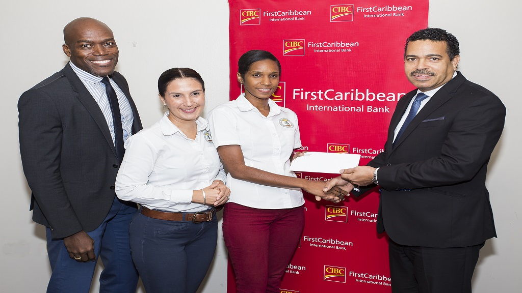JET Programme Director, Tamoy Singh Clarke (2nd right) accepts a cheque from CIBC FirstCaribbean's Managing Director Nigel Holness (right). The Bank's Chief Financial Officer, Lancelot Leslie (left) and JET Chief Executive Officer, Suzanne Stanley witness the presentation.