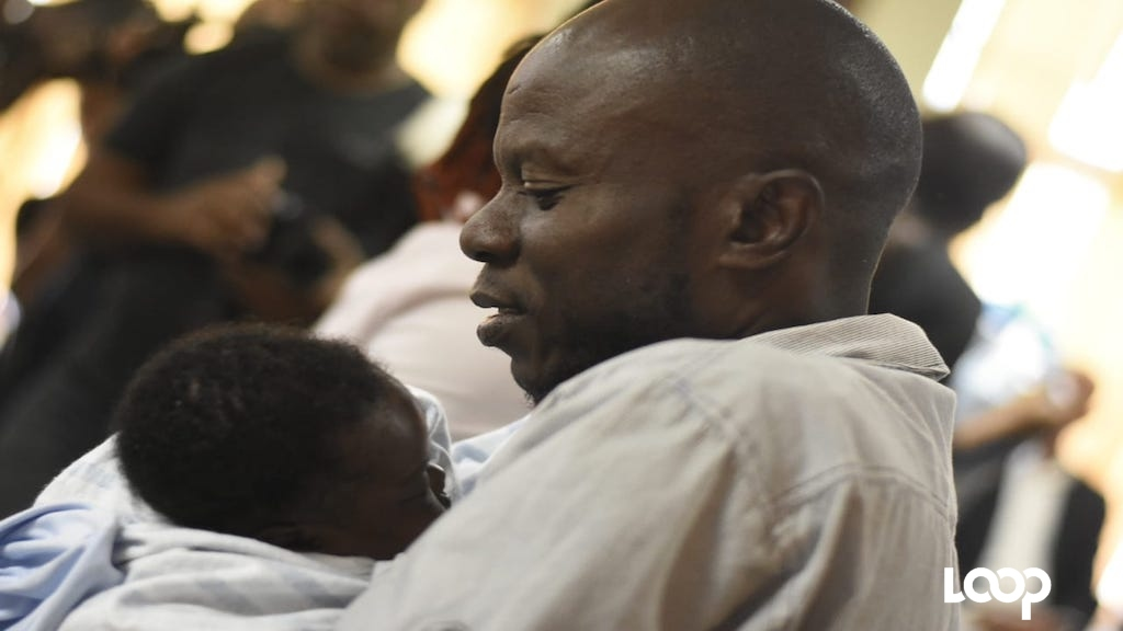 Sinclair Hutton cuddles his son, Sae'breon, after being reunited with the child on Friday. Sae'breon had been abducted from the Victoria Jubilee Hospital in Kingston last month. (PHOTO: Marlon Reid)