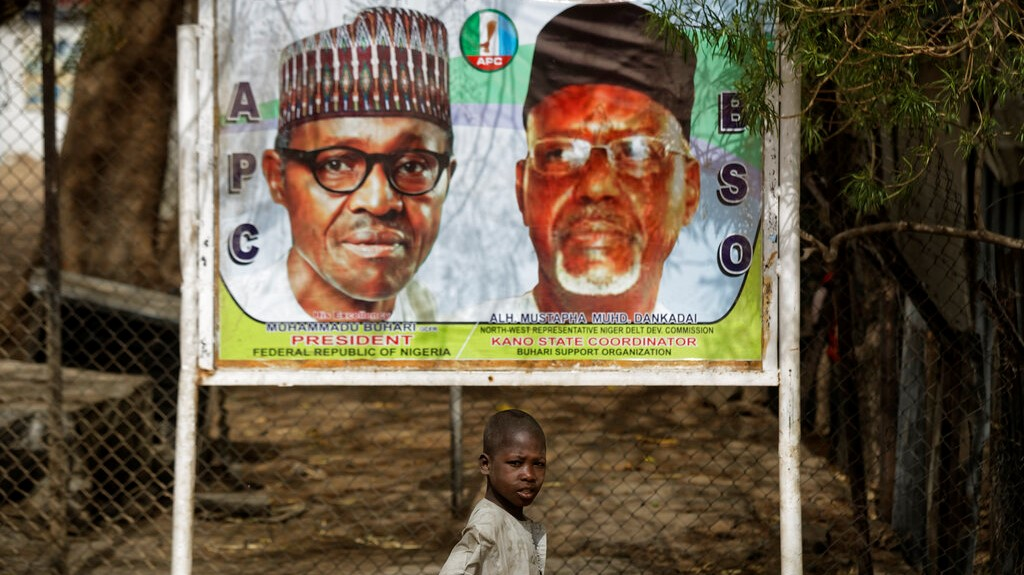 A young boy scavenges for re-sellable items from garbage on the streets, as he walks past a sign showing incumbent President Muhammadu Buhari, left, and local party official Mustapha Dankadai, right, in Kano, northern Nigeria Friday, Feb. 15, 2019. (AP Photo/Ben Curtis)