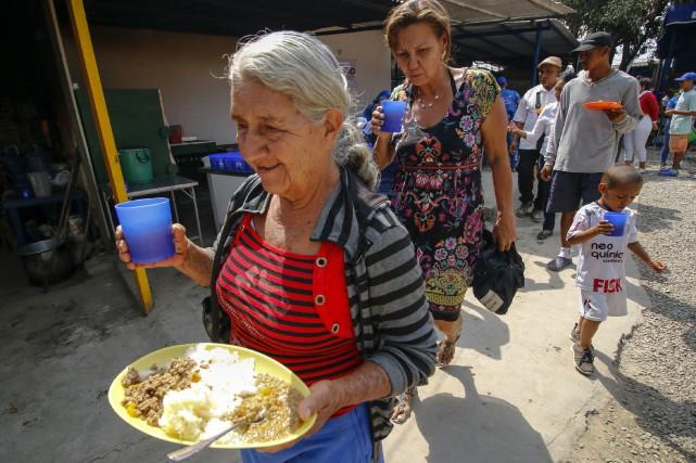 Des migrants vénézuéliens hébergés dans un refuge en Colombie, près de la frontière, profitent d'un repas suite à l'arrivée de l'aide humanitaire américaine.