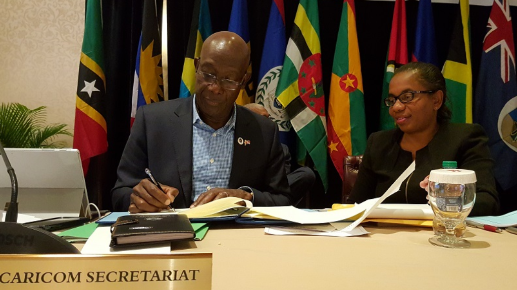 Prime Minister Dr Keith Rowley (left) signs CARICOM Multilateral Air Services Agreement in St Kitts and Nevis.