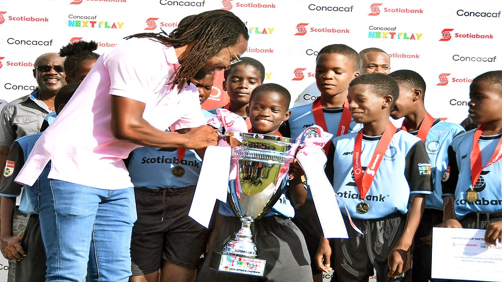 Concacaf Ambassador Ricardo Gardner (left) presents the inaugural Scotiabank/Concacaf  NextPlay Cup to members of the Holy Family Primary football team.