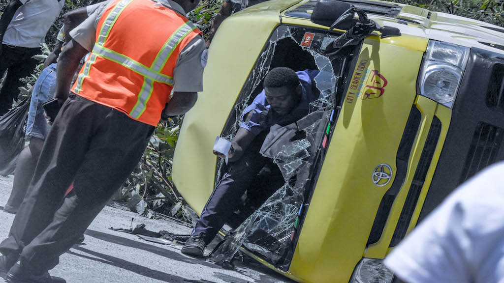 A driver steps out of a minibus after it overturned with him behind the steering wheel along Marcus Garvey Drive in Kingston on Monday afternoon. (Photo: Marlon Reid)