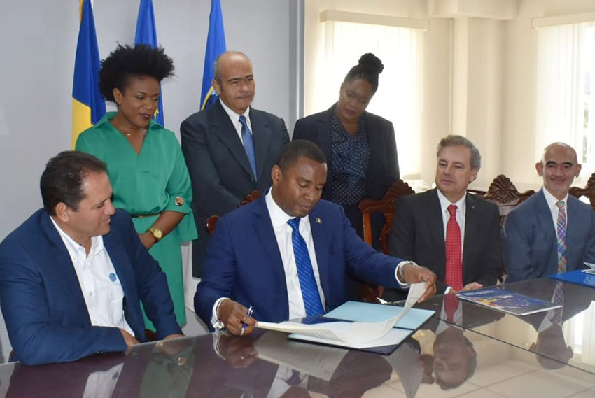 Minister of Energy and Water Resources, Wilfred Abrahams signing the document. Looking on are Ministers Marsha Caddle and William Duguid and various representatives and officials. (IDB/GP)