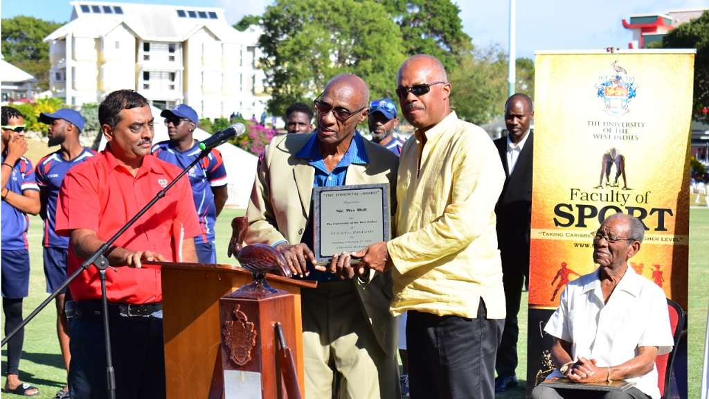 UWI Vice Chancellor Professor Hilary Beckles (right) presents legendary fast bowler Sir Wes Hall with a Tribute plaque from The University of the West Indies.