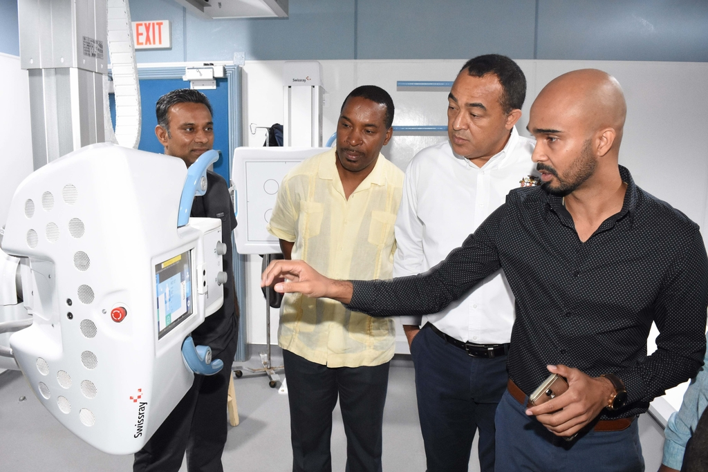 Health Minister, Dr Christopher Tufton  (2nd right), listens as Senior Software Architect and Research Engineer, Advanced Integrated Systems, Matthew Budram explains how the digital x-ray machine is incorporated with HIMS while, Medical Chief of Staff at the UHWI  Dr Carl Bruce (2nd left) and Dr Sundeep Shah, Consulting Radiologist of UHWI (left) looks on.