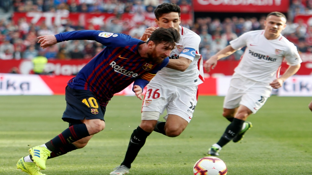 Barcelona forward Lionel Messi and Sevilla's Jeus Navas fight for the ball during a La Liga football match against Sevilla at the Ramon Sanchez Pizjuan stadium in Seville, Spain, Saturday, February 23, 2019.
