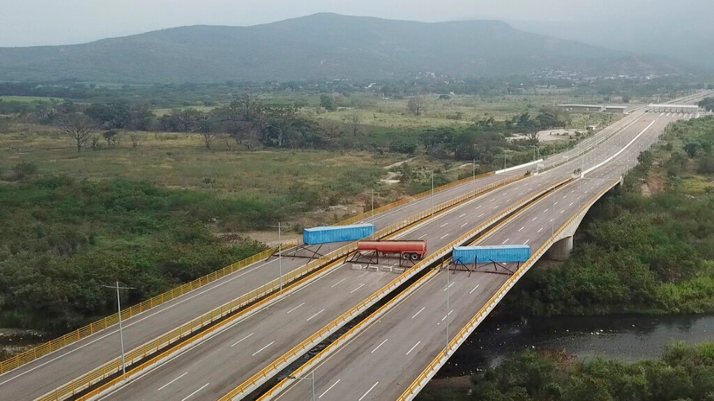 This Feb. 6, 2019 image taken from video, shows a fuel tanker, cargo trailers and makeshift fencing, blocking the Tienditas International Bridge in an attempt to stop humanitarian aid entering from Colombia, as seen from the outskirts of Cucuta, on Colombia's border with Venezuela. Immigration authorities say the Venezuelan National Guard built the roadblock a day earlier. (AP Photo)