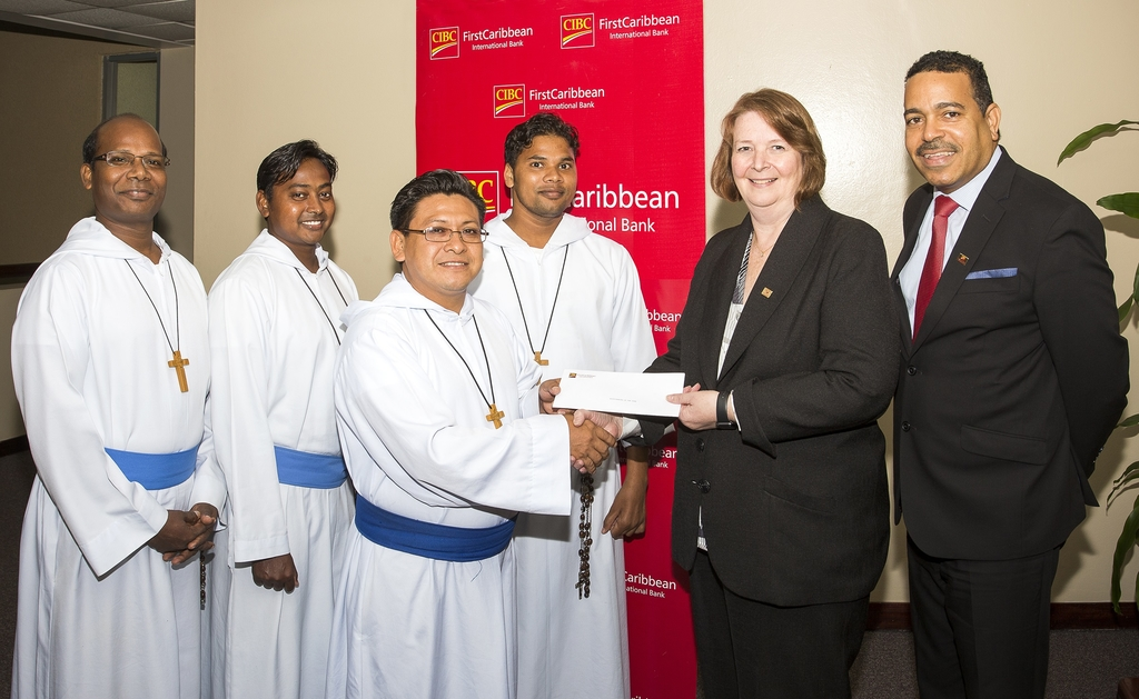 Colette Delaney (2nd right), CEO of CIBC FirstCaribbean International Bank and Nigel Holness (right), Managing Director of the bank present a cheque to Brother Vincent of Missionaries of the Poor.  Looking on are (l-r) Brothers Elijah, Anthony and Cyril.