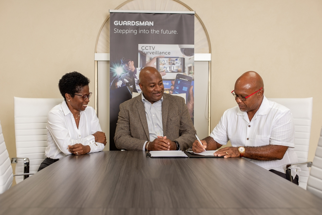 Ianthe Callender  (left), director of the Barbados-based Viking Security Systems, and Rudolph Green (centre) Guardsman Barbados' general manager look on as Hugh Callender, Viking's managing director, affixes his signature during the symbolic signing over of his company to Guardsman.