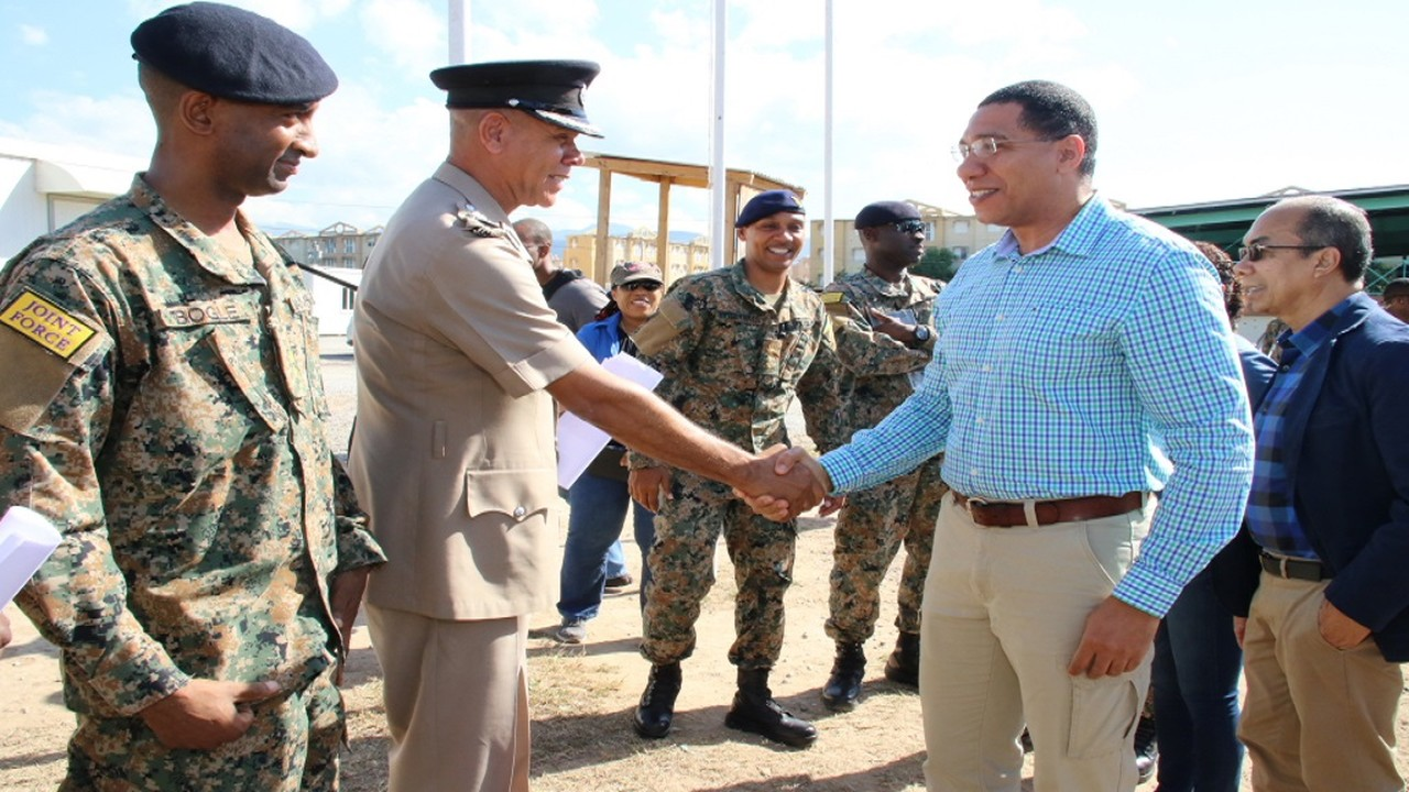 Prime Minister Andrew Holness (second right) greets police commissioner Major General Antony Anderson (second left) during a recent tour of a detention centre.