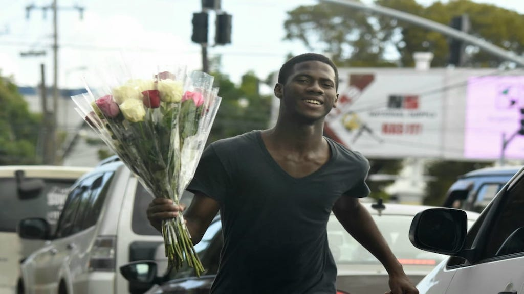 This vendor was all smiles as our lens caught him selling roses to Valentine's Day shoppers on Wednesday at the intersection of Waterloo and Hope roads in St Andrew. (PHOTO: Marlon Reid)