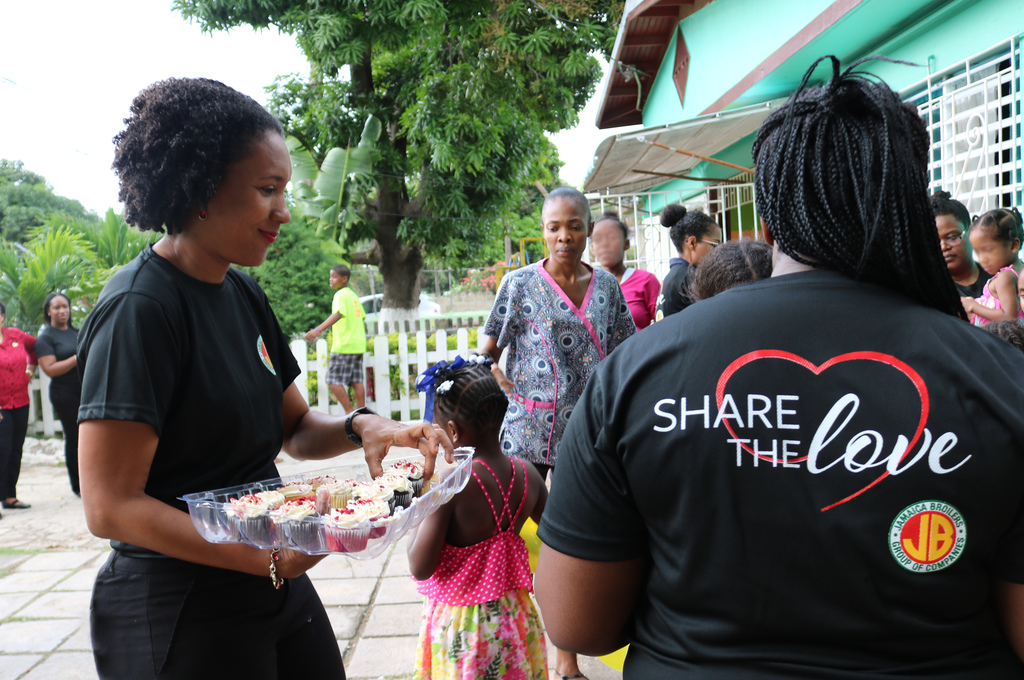 Danah Cameron, Group Public Relations Programmes Officer hands out cupcakes for dessert.