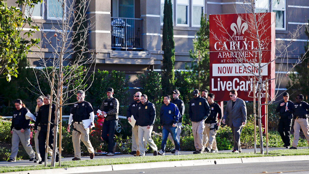 In this March 3, 2015 file photo, federal agents enter an upscale apartment complex where authorities say a birth tourism business charged pregnant women $50,000 for lodging, food and transportation, in Irvine, Calif. (AP Photo/Jae C. Hong, File)