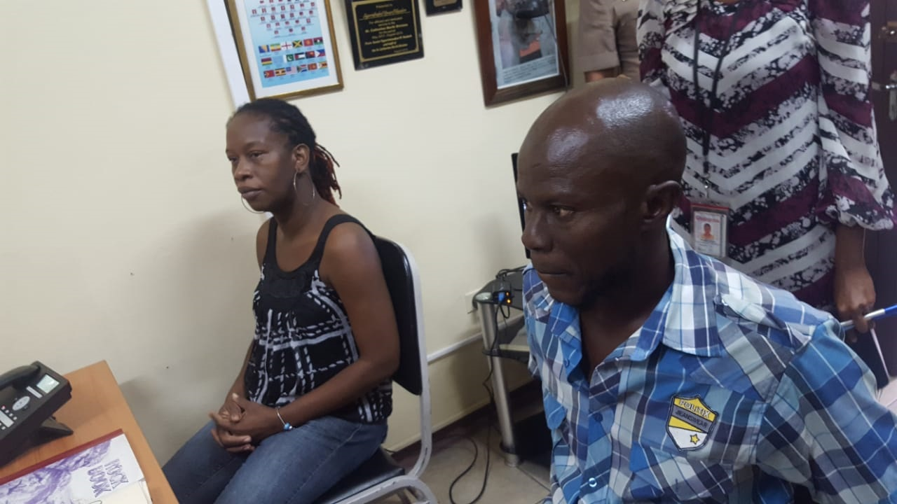 Suzette Whyte and Sinclair Hutton, mother and father of the baby that was stolen from the Victoria Jubilee Hospital last month, speak with officers at the Denham Town Police Station on Thursday.