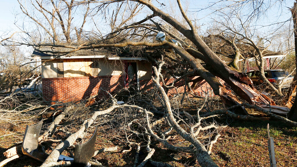 Tornado strewn debris and fallen trees take their toll in this Columbus, Miss., neighborhood, Sunday morning, Feb. 24, 2019. At least one person was killed among the shattered businesses and wrecked homes that dotted the South as severe storms followed a weekend of drenching rains and a rising flood threat. (AP Photo/Rogelio V. Solis)