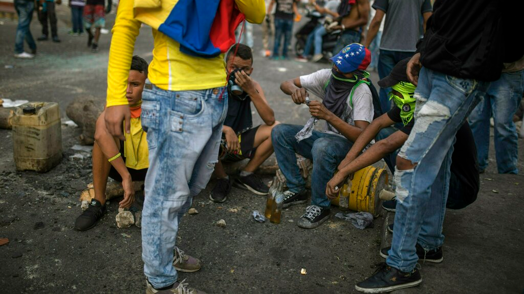 Demonstrators gather after clashing with the Bolivarian National Guard in Urena, Venezuela, near the border with Colombia, Saturday, Feb. 23, 2019. Venezuela's National Guard fired tear gas on residents clearing a barricaded border bridge between Venezuela and Colombia on Saturday, heightening tensions over blocked humanitarian aid that opposition leader Juan Guaido has vowed to bring into the country over objections from President Nicolas Maduro. (AP Photo/Rodrigo Abd)