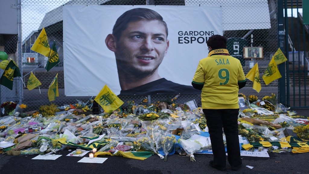 "In this Wednesday, Jan. 30, 2019, file photo, a Nantes football team supporters stops by a poster of Argentinian player Emiliano Sala and reading ""Let's keep hope"" outside La Beaujoire stadium before the French League One match between Nantes and Saint-Etienne, in Nantes, western France."