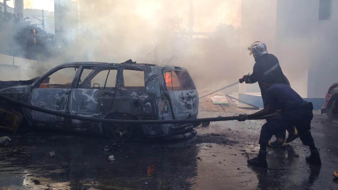 Un sapeur-pompier éteint les flammes ayant atteint une voiture sur la cour de la Télévision nationale d'Haiti (TNH)