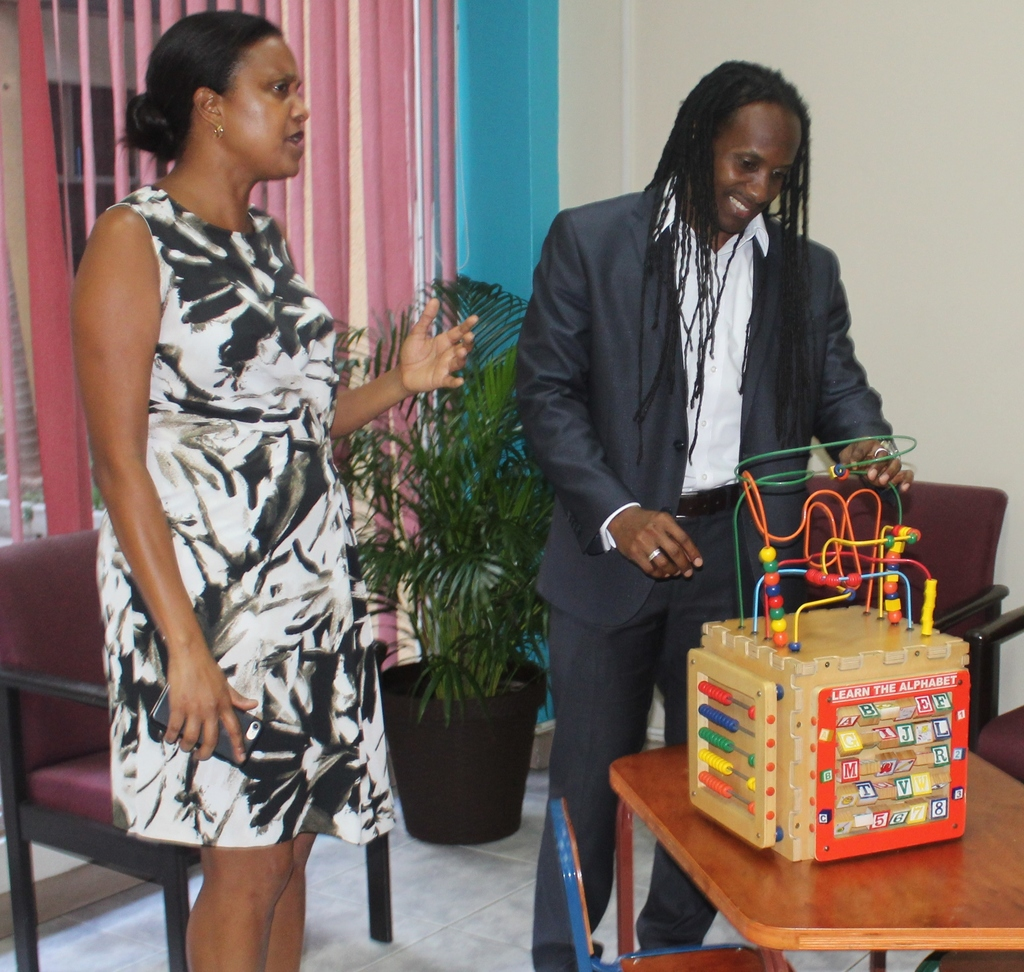 Chairman of the Early Childhood Commission, Trisha Williams-Singh explains the responsibilities and operation of the Early Childhood Commission to d State Minister in the Ministry of Education, Youth and Information, Alando Terrelonge.