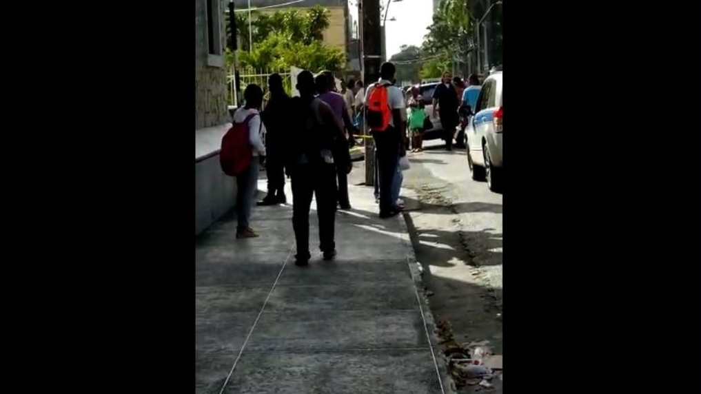 Pedestrians gather as police cordon off the scene of a shooting at Nelson Street, Port of Spain.