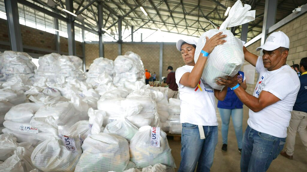 Venezuelan volunteers place a bag of USAID humanitarian aid for storage at a warehouse next to the Tienditas International Bridge, near Cucuta, Colombia, on the border with Venezuela, Friday, Feb. 8, 2019. Trucks carrying U.S. humanitarian aid destined for Venezuela arrived Thursday at the Colombian border, where opposition leaders vowed to bring them into their troubled nation despite objections from embattled President Nicolas Maduro. (AP Photo/Fernando Vergara)