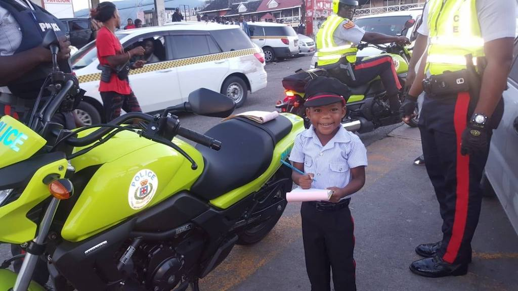 Young Jelani 'writes a ticket' after getting a chance to be police officer. (PHOTOS: JCF)