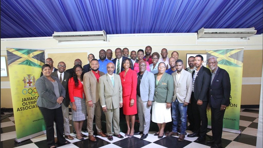 Jamaica Olympic Association (JOA) Board members and affiliates, headed by President Christopher Samuda (centre, front), who is flanked by General Secretary Ryan Foster and Office of the Children's Advocate chairperson, Diahann Gordon Harrison (red dress), huddle for a group photo during the recent JOA Sports for Breakfast Forum at Terra Nova hotel in Kingston.