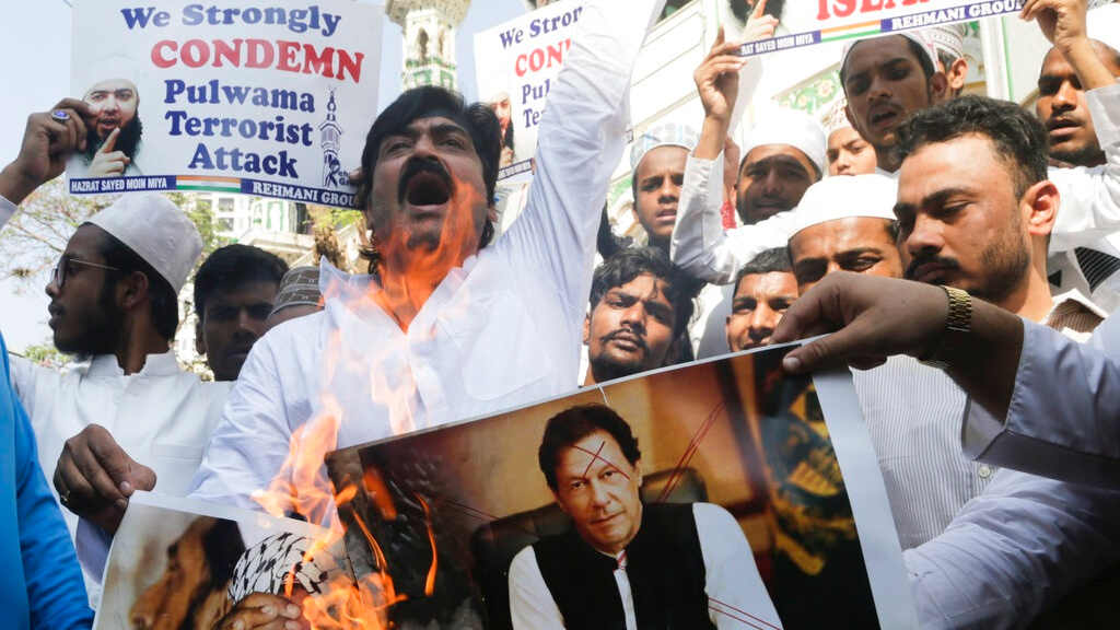 Indian muslims burn posters of Pakistani prime minister Imran Khan, center, and Jaish-e-Mohammed leader Masood Azhar, during a protest against Thursday's attack on a paramilitary convoy in Kashmir that killed at least 40, in Mumbai, India, Friday, Feb. 15, 2019.  (AP Photo/Rajanish Kakade)