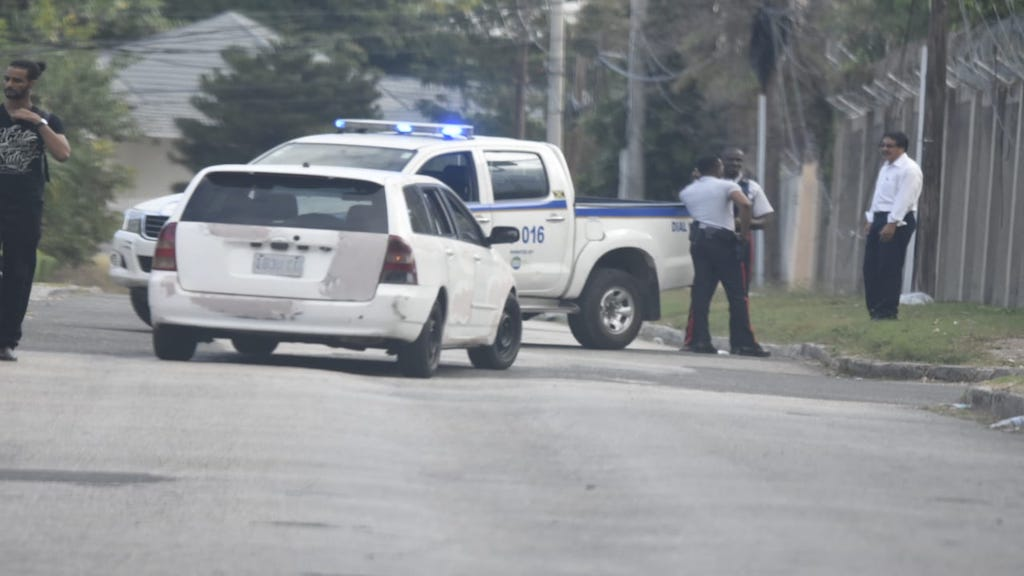 Detectives in the vicinity of Fit Farm Fitness Club in St Andrew where boxing trainer Christopher Brown was reportedly murdered. (PHOTOS: Marlon Reid)