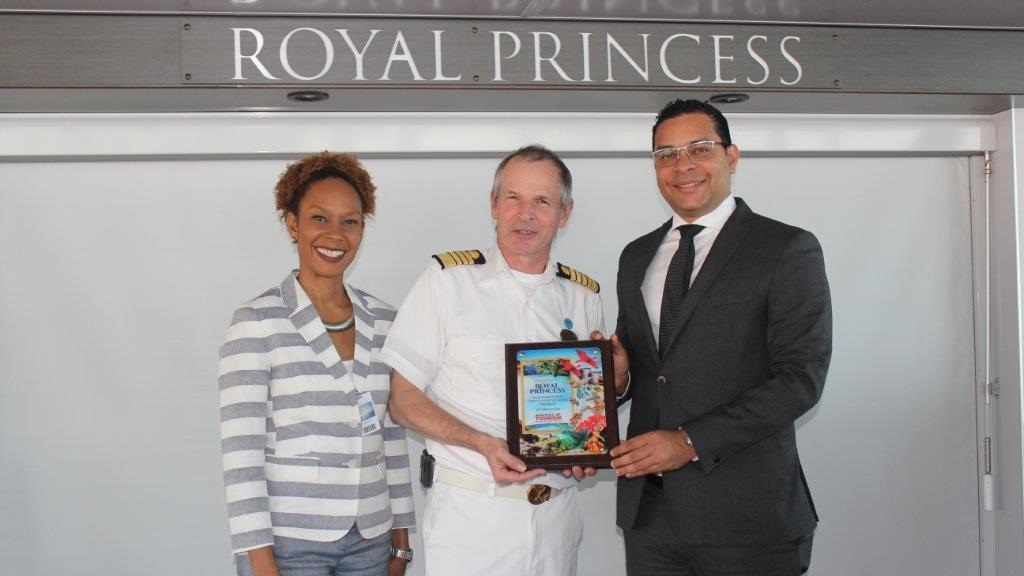 Tourism Minister Randall Mitchell presents Captain of the Royal Princess, Nicholas john Nash during Friday's Crest Exchange on the ship during its inaugural visit to the port of Port-of-Spain. Also in photo is Chief Executive of Tourism Trinidad Limited, Camille Campbell.