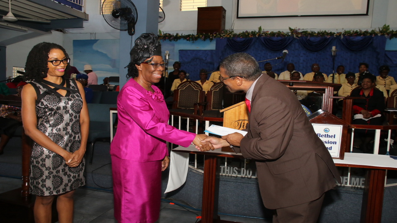 Petroleum Corporation of Jamaica's CFO, Robert Clarke presents a cheque to Bethel United Associate Pastor, Gene Hylton, during the PCJ's 15th anniversary celebration for its Schools Energy Programme. PCJ's corporate affairs and communication manager, Cammille Taylor shares in the occasion. (PHOTOS: Llewellyn Wynter)