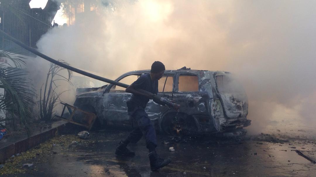 A Delmas 33, un sapeur pompier combat les flammes après que des manifestants ont incendié des véhicules sur la cour de la Télévision Nationale d'Haïti (TNH) / Photo: Steven Aristil