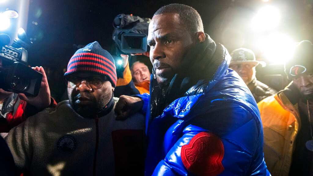 R. Kelly surrenders to authorities at Chicago First District police station, Friday, Feb. 22, 2019. R&B star R. Kelly was taken into custody after arriving Friday night at a Chicago police precinct, hours after authorities announced multiple charges of aggravated sexual abuse involving four victims, including at least three between the ages of 13 and 17. (Tyler LaRiviere/Chicago Sun-Times via AP)