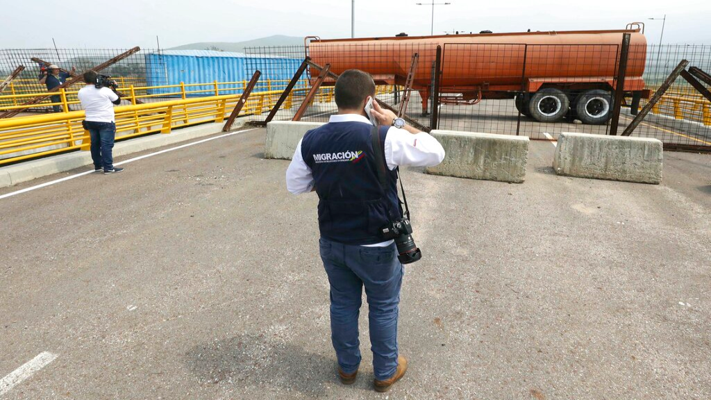 An immigration official observes a fuel tanker, cargo trailers and makeshift fencing, used as barricades by Venezuelan authorities attempting to block humanitarian aid entering from Colombia on the Tienditas International Bridge that links the two countries as seen from the outskirts of Cucuta, Colombia, Wednesday, Feb. 6, 2019. (AP Photo/Fernando Vergara)