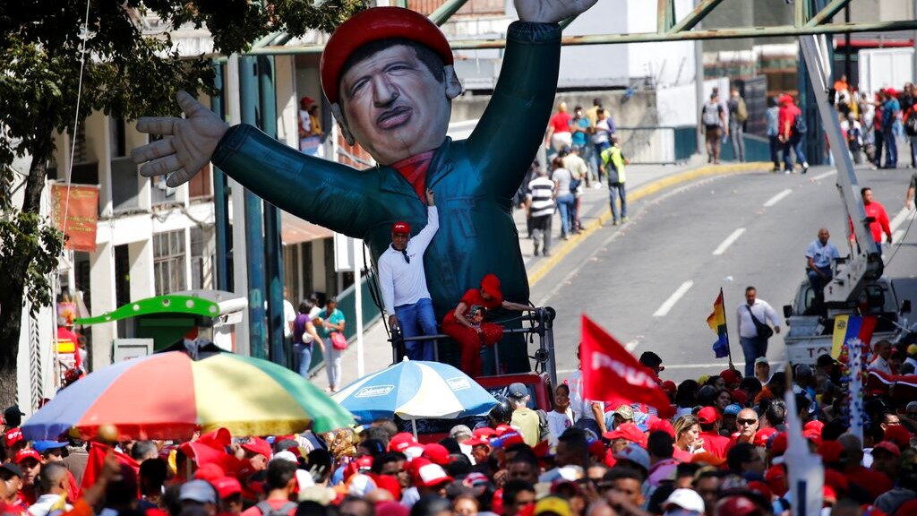 An inflatable doll depicting Venezuela's late President Hugo Chavez stands outside of Miraflores presidential palace, during a march of in defense of the state-run oil company PDVSA, in Caracas, Venezuela, Thursday, Jan. 31, 2019. (AP Photo/Ariana Cubillos)
