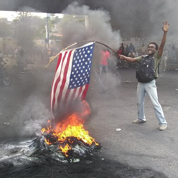 Illustration d'un manifestant brûlant le drapeau des Etats-Unis d'Amérique au carrefour de l'aéroport ce vendredi 15 février 201