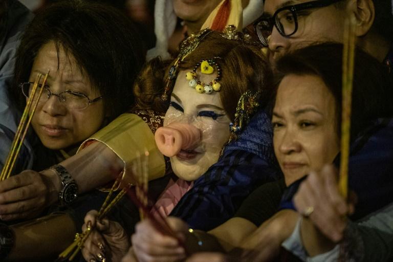Des gens regardent une danse du Lion devant un temple pour fêter le Nouvel An chinois, le 4 février 2019 à Medan (Indonésie)