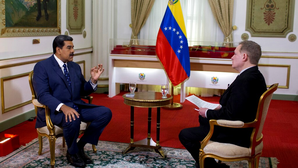 Venezuela's President Nicolas Maduro, left, speaks during an interview with Associated Press Vice President of International News, Ian Phillips, at Miraflores presidential palace in Caracas, Venezuela, Thursday, Feb. 14, 2019. (AP Photo/Ariana Cubillos)